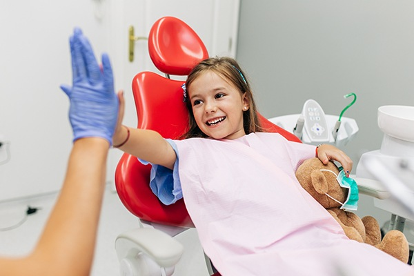 cute girl is high five with her south surrey Child is showing the white teeth with Pediatric Dentist