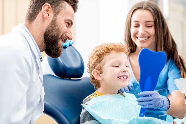 Child is showing the white teeth with Pediatric Dentist
